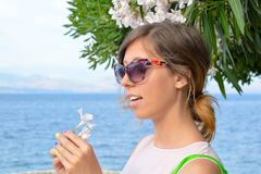 Brunette girl holding a white flower with seaside in background Royalty Free Stock Images