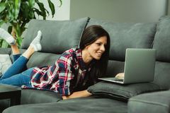 Brunette girl at home with a laptop. Royalty Free Stock Image