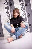 Brunette girl in jeans sitting on floor with legs crossed Stock Images
