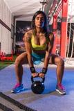 Brunette girl kettlebell swing weightlifting Stock Image