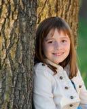 Brunette girl leaning against tree Royalty Free Stock Images