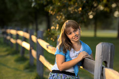 Brunette girl leaning against wooden fence Stock Image
