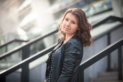Brunette girl in leather coat against urban landscape Royalty Free Stock Photos