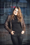 Brunette girl in leather jacket leaning against metal grid Stock Images