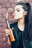 Brunette girl lighting up a cigarette from Molotov cocktail bomb in her hand Royalty Free Stock Photo
