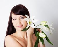 Brunette girl with lily flower in hand Royalty Free Stock Photo
