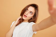 Brunette girl with long hair dressed in white t-shirt makes a selfie on the beige background in the studio stock photos
