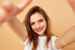 Brunette girl with long hair dressed in white t-shirt makes a selfie on the beige background in the studio royalty free stock image