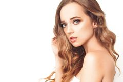 Brunette girl with long and shiny long hair . Beautiful model woman with curly hairstyle and fashionable makeup. Care and beauty of hair. Portrait of female royalty free stock images
