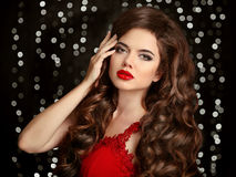 Brunette girl with long shiny wavy hair. Red lips. Beauty makeup Stock Photography