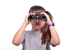 Brunette girl looking through binoculars Stock Images