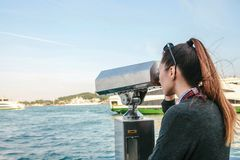 Girl looking at the sea through tourist telescope. View of the Bosphorus, Istanbul, Turkey. Vacation, travel. Brunette girl looking at the sea through tourist Stock Photography