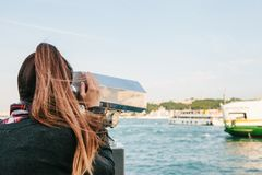 Girl looking at the sea through tourist telescope. View of the Bosphorus in Istanbul, Turkey. Brunette girl looking at the sea through tourist telescope Royalty Free Stock Photos