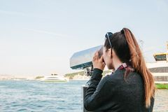 Girl looking at the sea through tourist telescope. View of the Bosphorus in Istanbul, Turkey. Brunette girl looking at the sea through tourist telescope Royalty Free Stock Image