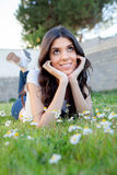 Brunette girl lying on the grass with daisies around thinking Royalty Free Stock Photography