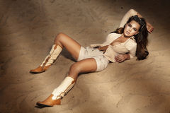 Brunette girl lying on the sand. Beautiful brunette woman lying on the sand, looking at camera Royalty Free Stock Images