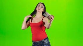 Brunette girl making selfie photo using a smartphone. Green screen stock video