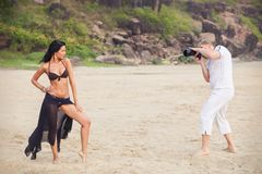 Brunette girl and man in white. Brunette girl in brown bra and style black skirt posing to photographer standing  on the beach sand with rocks background Stock Images
