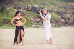 Brunette girl and man in white. Man in white getting some photographs of a brunette girl in brown bra and style black skirt standing  on the beach sand with Stock Photos