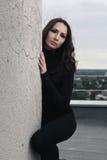 Brunette girl near wall Stock Images