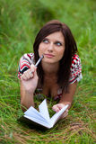 Brunette girl with notebook and pen thinking Stock Photo
