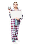 Brunette girl in pajamas holding a poster and showing alarm cloc Stock Photo