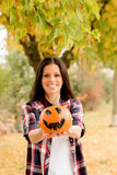 Brunette girl in a park with a Halloween pumpkin Royalty Free Stock Image