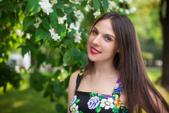 Brunette girl in the park wearing black dress with flowers Royalty Free Stock Photo