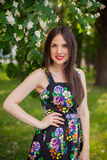 Brunette girl in the park wearing black dress with flowers Stock Image
