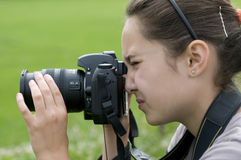 Brunette girl photographer. Beautiful teenage brunette girl taking photos Stock Images