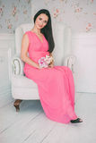 Brunette girl in pink dress sitting white armchair with bouquet of flowers in their hands Royalty Free Stock Image