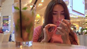 Brunette girl in pink using her mobile phone in a cafe. Modern mobile phone addiction. 4K clip stock footage