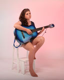 Brunette girl playing blue guitar Stock Image