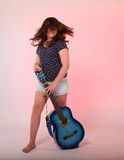 Brunette girl playing blue guitar Royalty Free Stock Photos