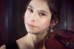 Brunette Girl playing violinover dark background Royalty Free Stock Photo
