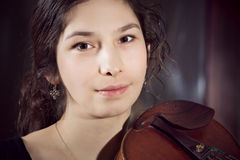 Brunette Girl playing violinover dark background Royalty Free Stock Photography