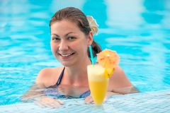 Brunette girl in the pool and a glass of cocktail royalty free stock photos
