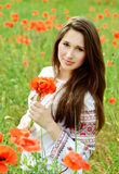 Brunette girl in poppes field Royalty Free Stock Photo
