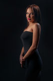 Brunette girl posing on dark background Royalty Free Stock Photos