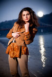 Brunette girl posing at evening against moonlight and sea Stock Photo