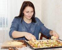 Brunette girl preparing a pizza Stock Images