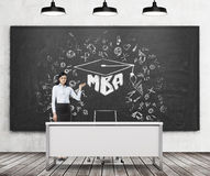 A brunette girl presents MBA sketch on the black chalk board in a modern classroom. Three black ceiling lights, wooden floor and c Stock Photography