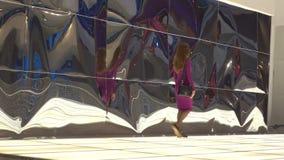 Brunette girl in purple dress walking agaist distorting reflective wall. 4K video stock video