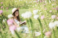 Brunette girl read book at flower field. Portrait of beautiful Asian woman with hat read book at grass field with white and pink flowers in morning. Outdoor royalty free stock image