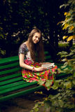 Brunette girl reading book on bench at park Stock Photo