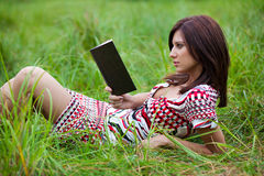 Brunette girl reading book lying on the grass Stock Image