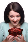 Brunette girl receiving a gift. Brunette girl looking down joyfully at a received gift royalty free stock images