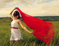 Brunette girl with red fabric in summer day Stock Image