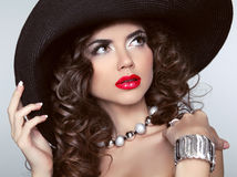 Brunette girl with red lips, makeup, wavy hair, fashion jewelry. Royalty Free Stock Image
