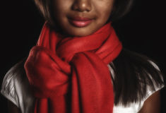 Brunette girl in a red scarf around his neck close-up. On a black background Stock Image